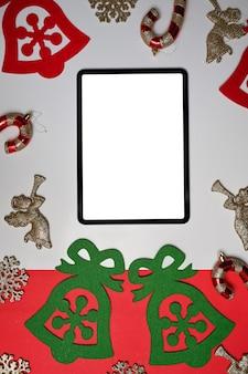 흰색과 빨간색 배경에 크리스마스 장식이 있는 디지털 태블릿을 비웃습니다.