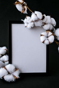 Макет высушенных цветов хлопка и белая рамка на уютном черном фоне. плоская планировка. копировать пространство.