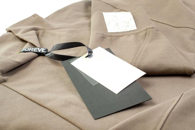 Макет пустой черно-белой бумажной бирки, прикрепленной к воротнику с черной атласной лентой и нашивкой с логотипом бренда на изолированном рукаве.