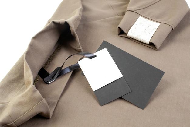 Макет пустой черно-белой бумажной бирки, прикрепленной к воротнику черной атласной лентой и нашивкой с логотипом бренда на рукаве.