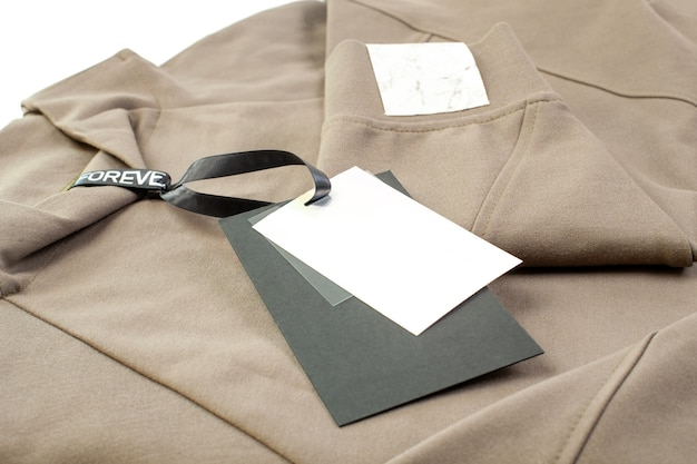 Mock up empty black and white paper tag attached to the collar with a black satin ribbon and a patch for the brand logo on the sleeve isolated