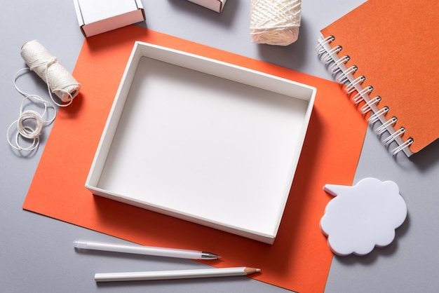 Mock up, empty carton box top view on orange background with stationary