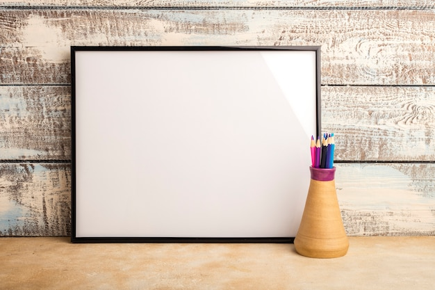 Mock up of an empty frame poster on a wall of wooden boards. color pencils in a vase. copy space