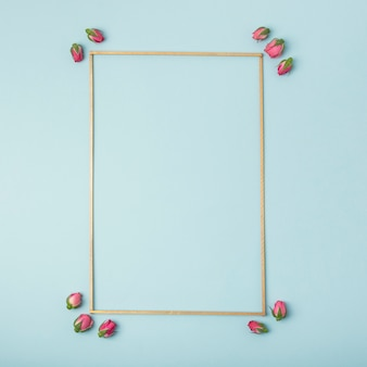 Mock-up empty frame with rosebuds on blue background