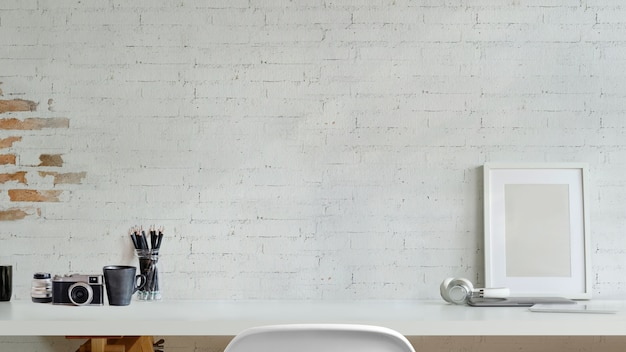 Mock up frame, camera on desk over white brick wall. workspace and copy space