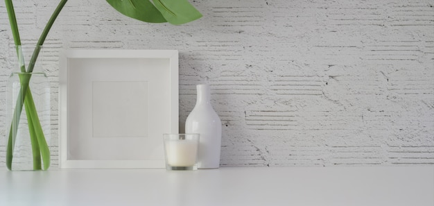 Mock up frame with decorations in minimal office room on white table and white brick wall