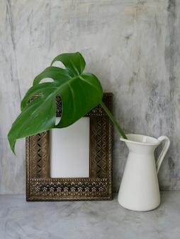 Mock up frame with green tropical leaf in vase, copy space