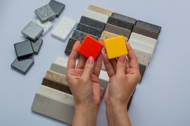 Макет из натуральных камней, вид сверху, крупный план. женские руки рекламируют материалы для ремонта. напольная плитка, кафель, столешницы.