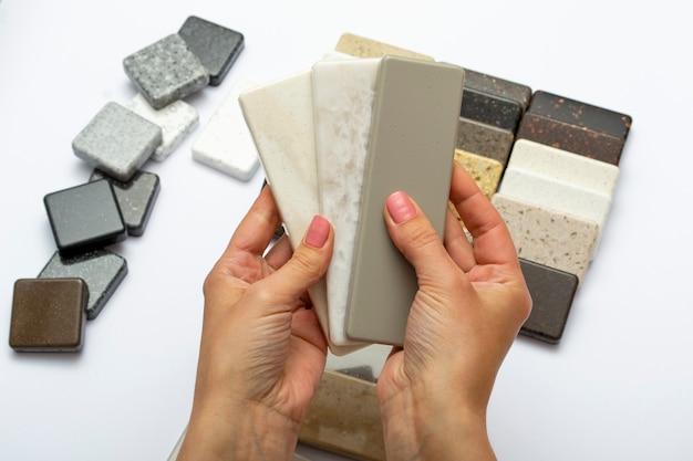 天然石、上面図、クローズアップからモックアップ。女性の手は修理材料を宣伝しています。床タイル、タイル、カウンタートップ。