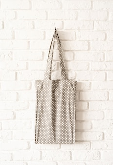 Mock up gray dotted tote bag eco hipster white cotton fabric on white brick wall background. copy space
