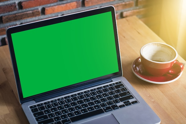 Mock-up green laptop screen monitor on wooden table