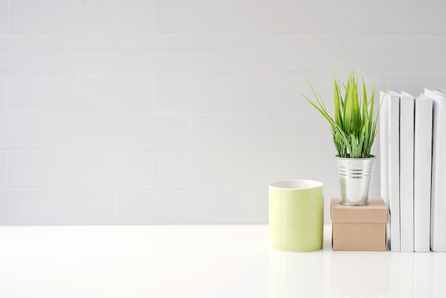 Mock up green mug, paper box, houseplant and books on white table with white brick wall
