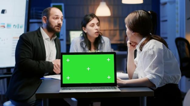 회의실의 테이블 회의에 격리된 디스플레이가 있는 녹색 화면 크로마 키를 조롱합니다. 경영 전략 기획 회사 프레젠테이션을 논의하는 다양한 다민족 기업인
