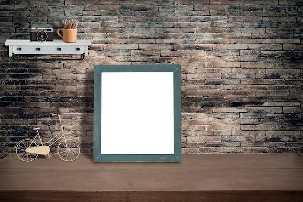 緑の木製の写真のフレームと古いレンガの壁が付いている木製のテーブルの上の消耗品をモックアップ