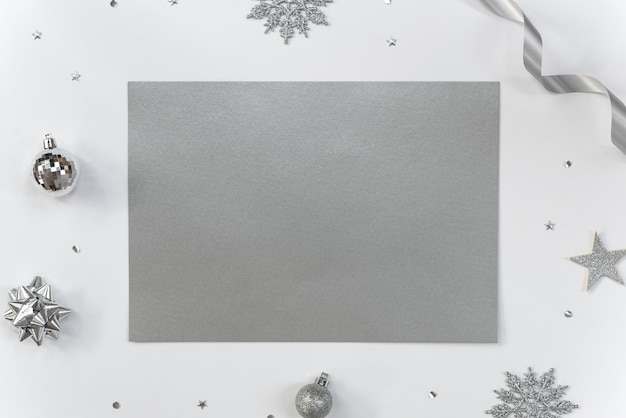 Mock up greeting paper card on white  with christmas decorations and confetti.