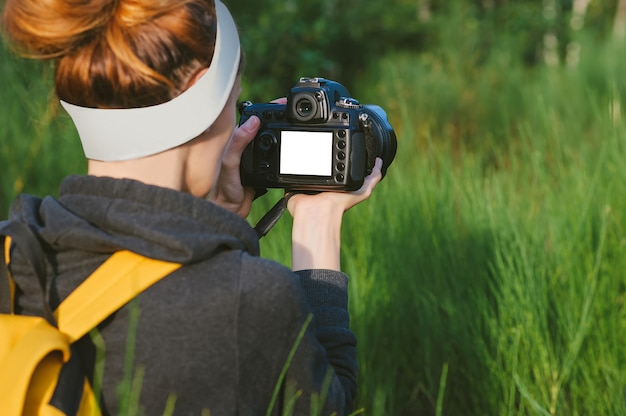 Mock-up in the hands of a girl with a reflex camera in the forest. against the backdrop of beautiful greenery.