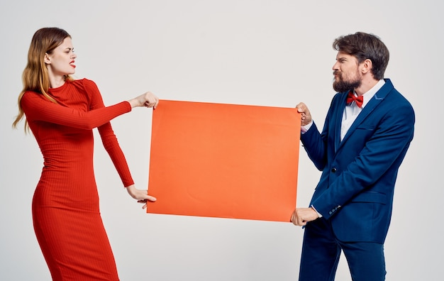 Mock up in the hands of a woman in a red dress and an emotional man in a suit