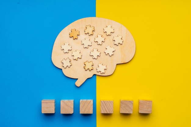 Mock up of a human brain with scattered puzzle pieces on a yellow and blue background. six cubes in which you can write the word autism in your font.
