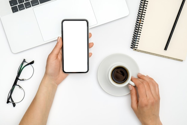 Mock up image of female hand holding and using mobile phone with blank screen