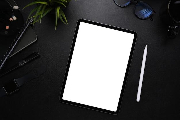 현대적인 어두운 작업 공간에서 빈 화면, 스타일러스 펜, 스마트 시계, 안경 및 노트북이 있는 디지털 태블릿의 이미지를 조롱합니다.