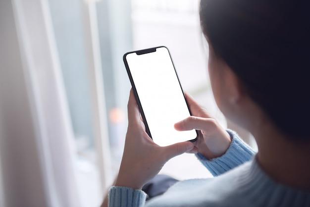 Копируйте изображение руки, касающейся мобильного смартфона пустым белым экраном в домашнем интерьере, гостиной, копией пространства.