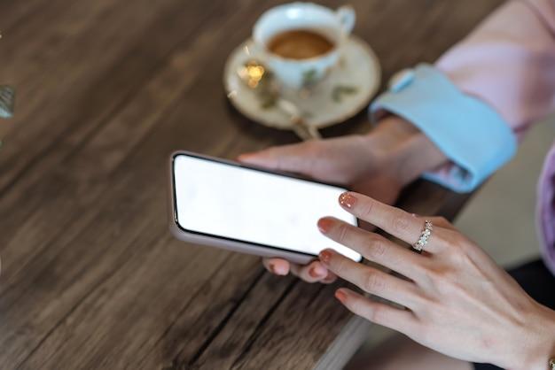 모의. 빈 흰색 화면으로 휴대 전화를 들고 여자의 이미지.