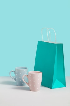 Mock up image with trending tea mugs near paper bag stand on blue background. gift concept image with space for design. gift shop. branding mock up. concept for sales or discounts, promotion