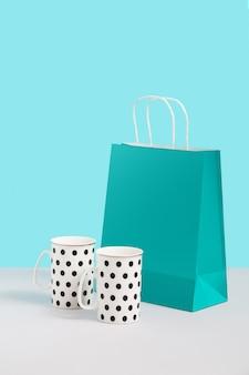 종이 가방 근처 유행 차 찻잔으로 이미지를 모의 파란색 배경에 서 서. 디자인을위한 공간을 가진 선물 개념 이미지입니다. 선물 가게. 브랜딩을 조롱하십시오. 판매 또는 할인, 프로모션에 대한 개념