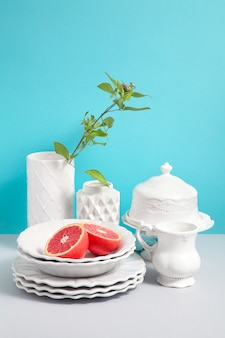 Mock up image with white stylish pottery and flower vases on grey table against blue background with space for design. image for shops of ceramic tableware. kitchen still life as background for design