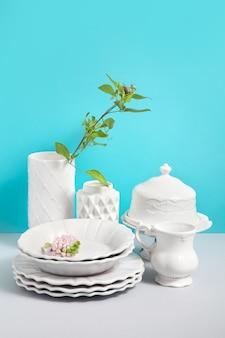 봉사를위한 흰색 식기 및 디자인을위한 공간으로 파란색 배경에 회색 테이블에 꽃 화병으로 이미지를 비웃는 다. 도자기 식기 상점 이미지. 정물화 개념.