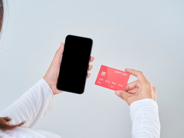 Mock-up image of woman hand holding mobile phone, blank screen and credit card on gray background