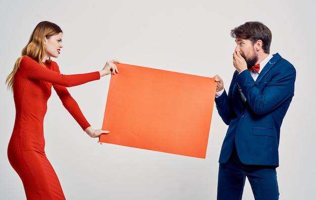 Макет в руках женщины в красном платье и эмоционального мужчины в костюме. фото высокого качества