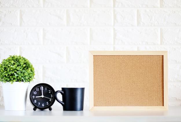 白いレンガの壁の背景に室内オフィスの木製のフレームのフレームポスターをモックアップ、
