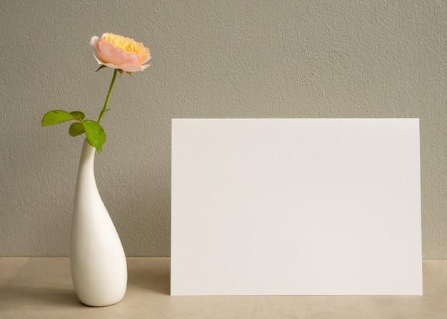 モダンな花瓶に招待状の白いカードと美しいバラの花をモックアップ