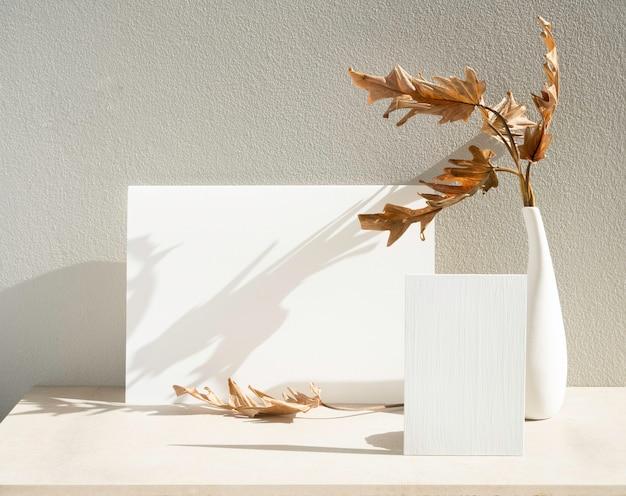 招待状の白いカードとエキゾチックなフィロデンドロンの乾燥した葉をコンクリートの背景を持つテーブルの上のモダンな花瓶にモックアップ