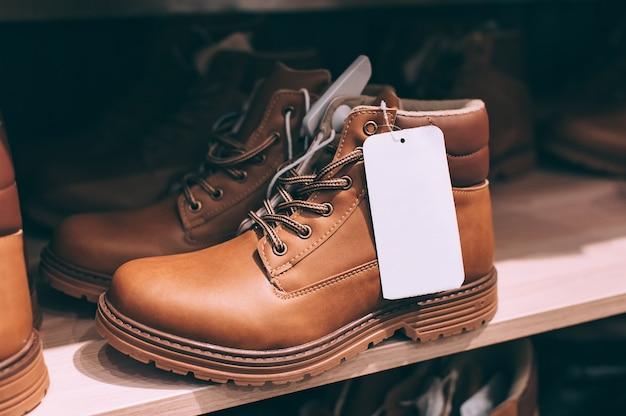 Макет этикетки на современной коричневой осенней и зимней обуви, на витрине в супермаркете.