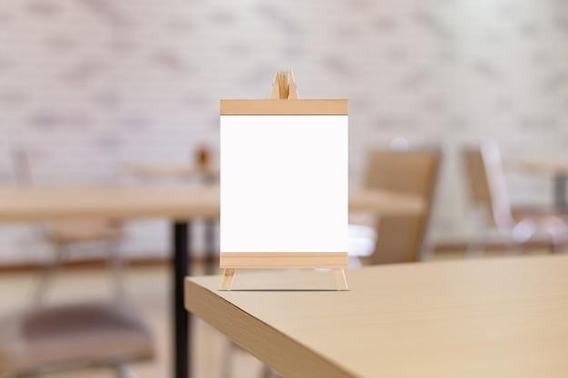 모의 업 바 레스토랑의 빈 메뉴 프레임에 레이블을 지정합니다. 배경이 흐린 테이블에 흰색 시트 종이 아크릴 텐트 카드가있는 소책자에 텍스트 또는 그림을 삽입 할 수 있습니다.