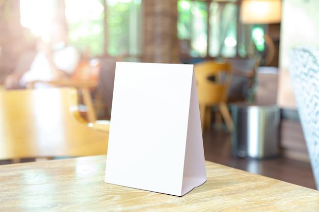 바 레스토랑에서 빈 메뉴 프레임에 레이블을 지정합니다. 흐릿한 배경이 있는 테이블에 흰색 시트 종이 아크릴 텐트 카드가 있는 소책자 스탠드는 텍스트나 그림을 삽입할 수 있습니다.