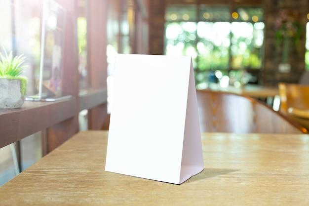 바 레스토랑에서 빈 메뉴 프레임에 레이블을 지정합니다. 흐릿한 배경이 있는 테이블에 흰색 시트 종이 아크릴 텐트 카드가 있는 소책자 스탠드는 텍스트나 그림을 삽입할 수 있습니다. 프리미엄 사진
