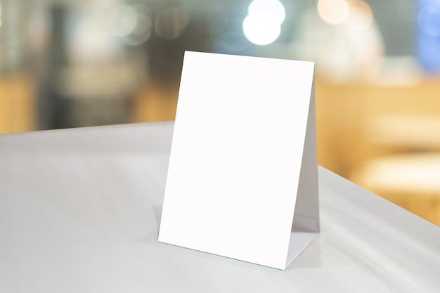 모의 업 바 레스토랑의 나무 테이블에 흰색 시트 종이 아크릴 텐트 카드로 빈 메뉴 프레임 또는 소책자에 라벨을 붙입니다. 고객의 텍스트를 삽입 할 수 있습니다.