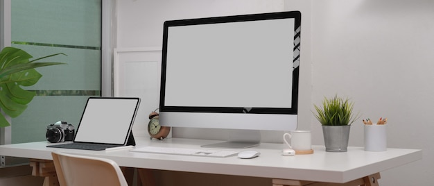 Mock up laptop, computer, camera and decorations on white desk in home office room