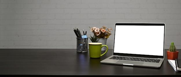 Копируйте портативный компьютер, кофейную чашку и подставку для карандашей на деревянном столе с кирпичной стеной.