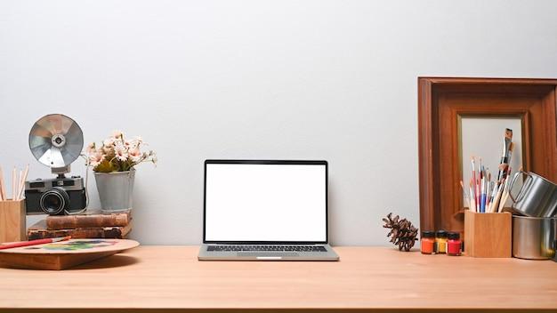 Копируйте портативный компьютер на деревянном столе на современном рабочем месте.