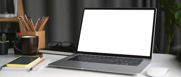 홈 오피스의 흰색 테이블에 빈 화면, 스마트 폰, 커피 컵이 있는 노트북 컴퓨터를 비웃으세요.