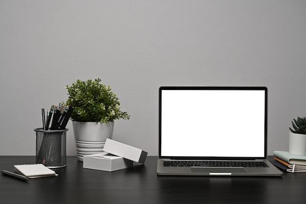 Копируйте портативный компьютер с белым дисплеем на черном столе в домашнем офисе.