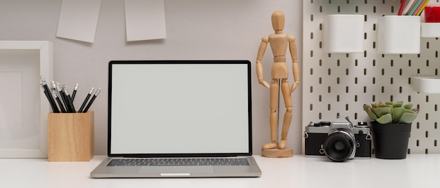 Mock-up laptop, stationery, camera and decoration on white table in home office