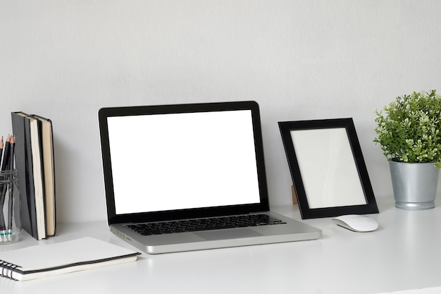 Mock up laptop on work space with photo frame, plat and jar of pencil copy space office.