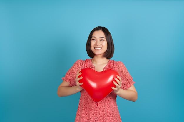 붉은 심장 모양의 풍선을 들고 웃는 만족 아시아 여자를 모의
