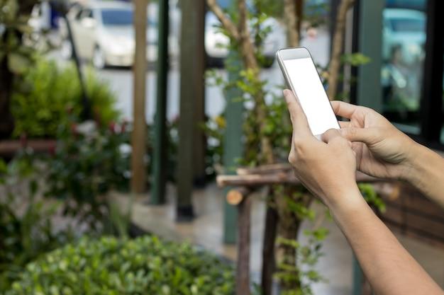 モックアップの男は、携帯電話の空白の白い画面をぼんやりショップと駐車場の背景を保持