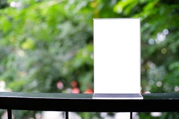 モックアップバーレストランカフェの木製テーブルに立っているメニューフレーム。テキストのスペース。